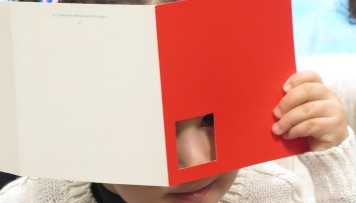 Enfant se cachant derrière un livre