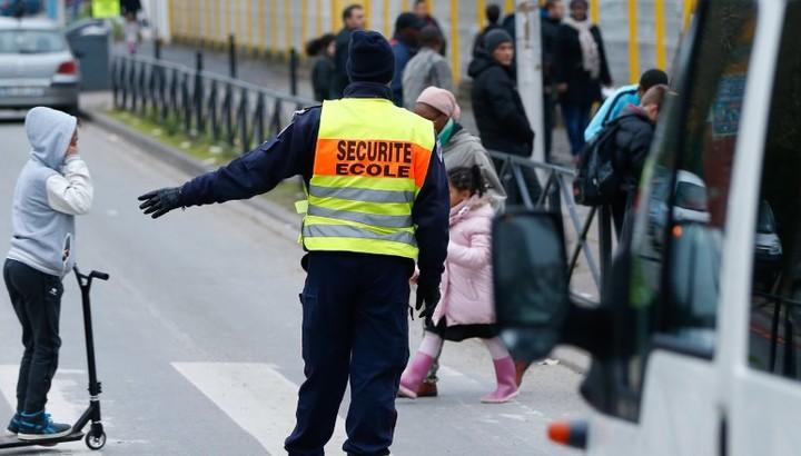 Policier municipal assurant la traversée des écoliers