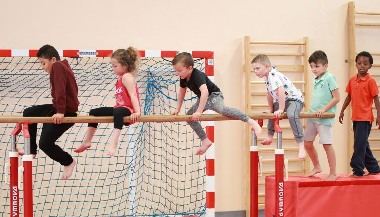 enfants aux barres parrallèles en gymnastique